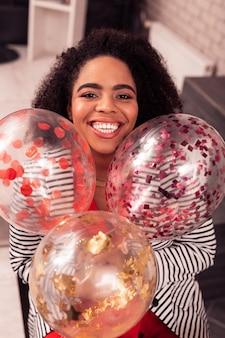 Alla festa. felice donna positiva sorridente mentre si tengono bellissimi palloncini