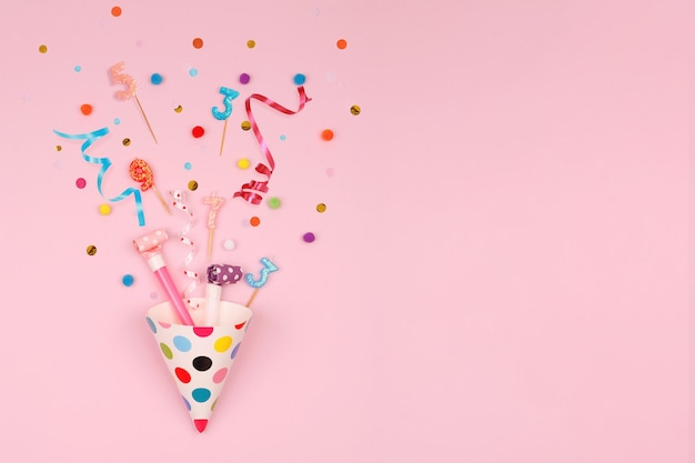 Coriandoli e candele del cappello da festa che si trovano su sfondo rosa