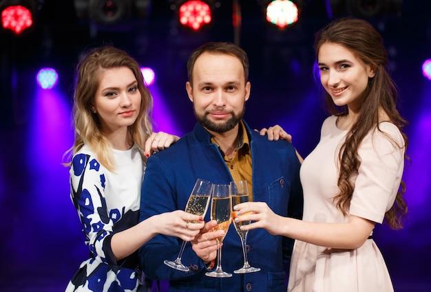 Concetto di festa, vacanze, celebrazione, vita notturna e persone - amici sorridenti con bicchieri di champagne nel club