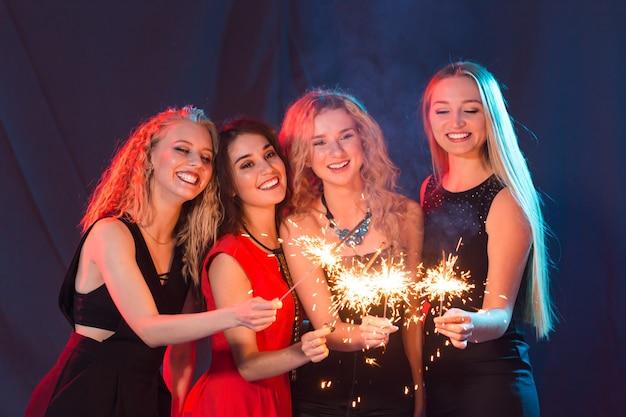 Vita notturna di feste di festa e concetto di capodanno giovani donne felici che ballano in discoteca night club