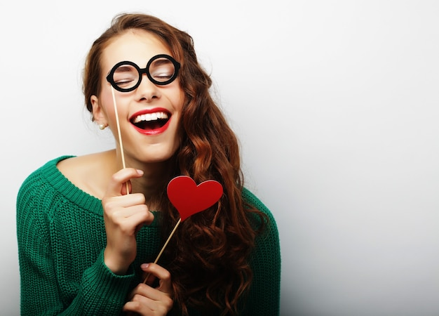 Immagine del partito. giovane donna allegra che tiene gli occhiali da festa.