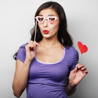 Immagine del partito. giovane donna allegra che tiene un cuore del partito.