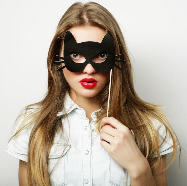 Immagine del partito. giovane donna allegra che tiene una maschera del partito. pronto per il buon tempo.