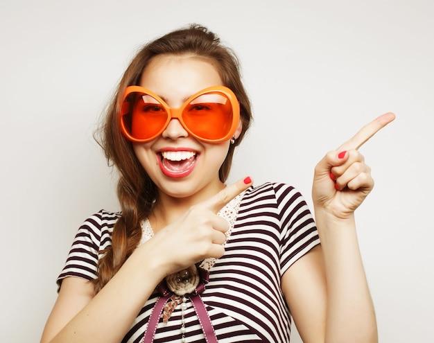 Immagine del partito. giocosa giovane donna con grandi bicchieri da festa e corona. pronto per il buon tempo.