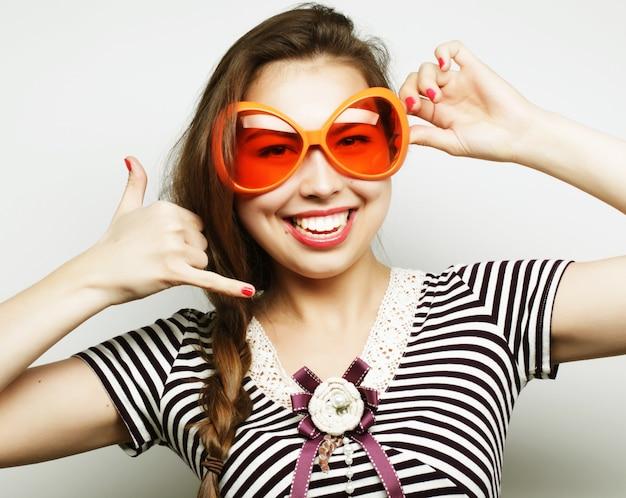 Immagine del partito. giocosa giovane donna con grandi bicchieri da festa e corona. pronto per il buon tempo. Foto Premium