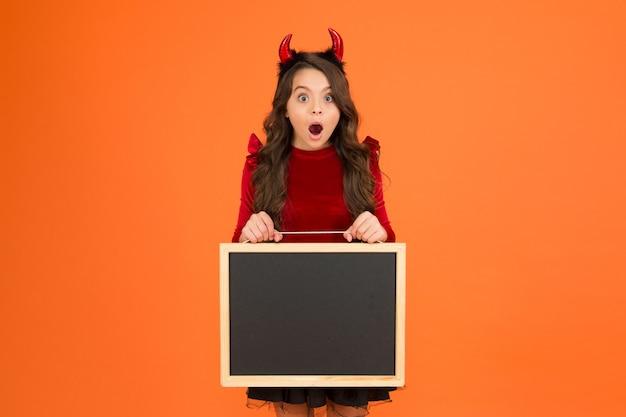 La festa è iniziata. tabellone informativo per bambini sorridenti. divertiti. benvenuto alla festa di carnevale. felice halloween. saldi per le vacanze autunnali. copia spazio. piccola lavagna della scuola della ragazza. corna rosse da diavoletto.