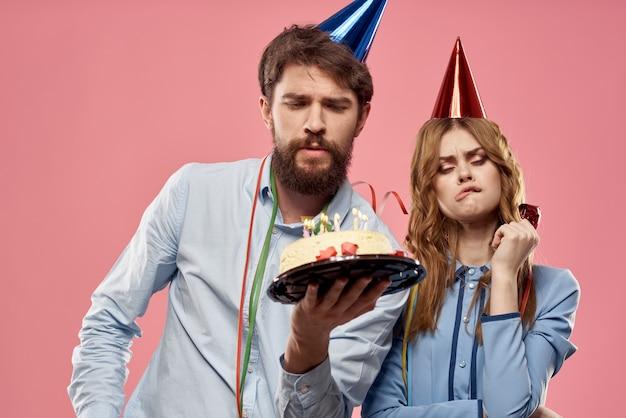 Partito uomo e donna con torta sul compleanno aziendale sfondo rosa
