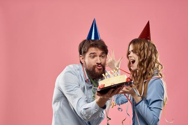Uomo e donna di partito con la torta sul compleanno aziendale rosa