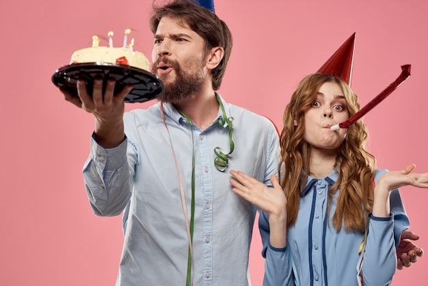 Uomo e donna di partito con la torta sulla parete rosa