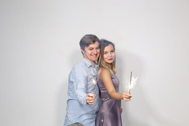 Concetto di festa, capodanno e vacanze - giovani coppie che celebrano il loro anniversario con stelle filanti su sfondo bianco