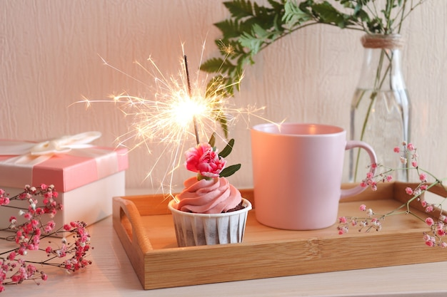 Tempo di festa bigné di compleanno con sparkler, tazza di caffè sul vassoio in legno