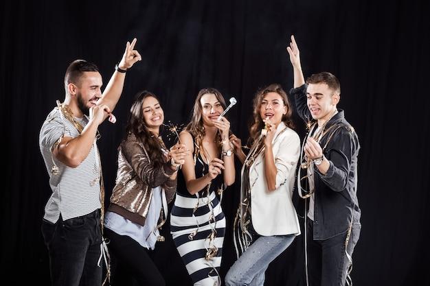Tempo di festa. compagnia di amici in abiti casual alla moda si divertono con nastri e tubi e stelle filanti su uno sfondo nero in studio.