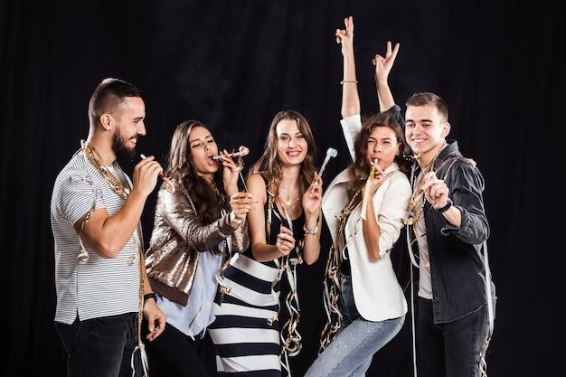 Tempo di festa. compagnia di amici in abiti casual alla moda gioire e divertirsi su uno sfondo nero in studio.
