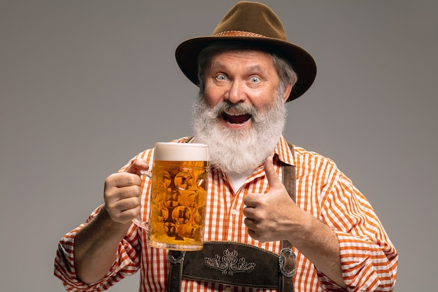 Tempo di festa. felice uomo anziano vestito in costume tradizionale austriaco o bavarese con boccale di birra su sfondo grigio studio. copyspace. la celebrazione, l'oktoberfest, il festival, il concetto di tradizioni.