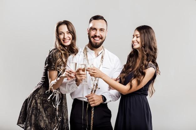 Tempo di festa. due belle ragazze vestite con abiti eleganti e un bell'uomo con la camicia bianca tengono bicchieri di champagne.