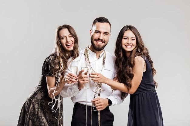 Tempo di festa. due belle ragazze vestite con abiti eleganti ed eleganti e un bell'uomo con la camicia bianca sorridono e tengono in mano bicchieri di champagne.