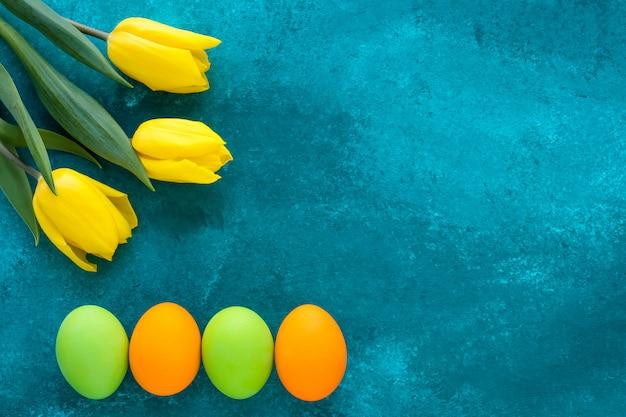 Carta regalo pasquale con uova dipinte luminose e tulipani gialli su sfondo turchese scuro grunge. cornice di pasqua festiva con spazio di copia.