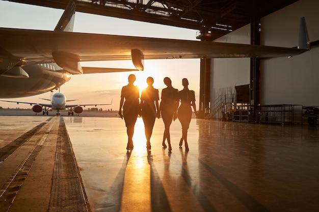 Aereo passeggeri nell'hangar e quattro assistenti di volo femminili esili che camminano vicino ad esso. grande aereo all'aperto sullo sfondo