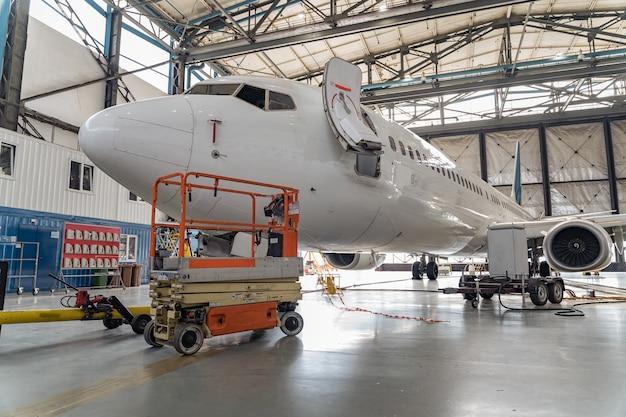 Aerei passeggeri sulla manutenzione del motore e riparazione della fusoliera nell'hangar