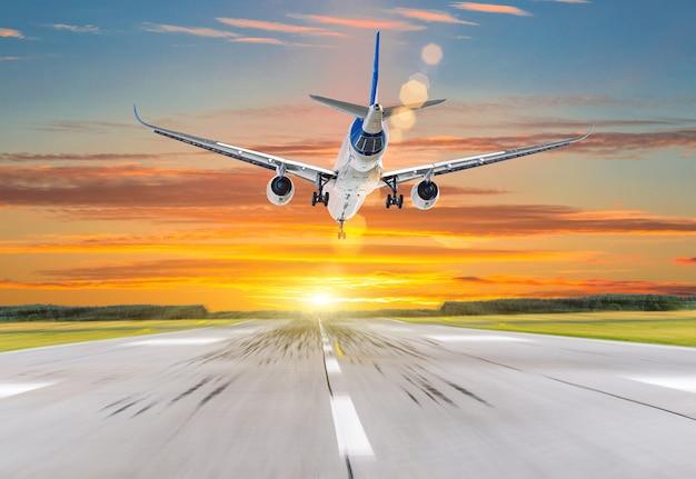 Atterraggio aereo passeggeri al tramonto su una pista.