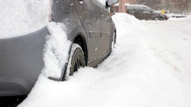 Autovettura bloccata nella neve, vista laterale. auto bloccata nel cortile da un cumulo di neve dopo una forte bufera di neve. condizioni meteorologiche avverse.