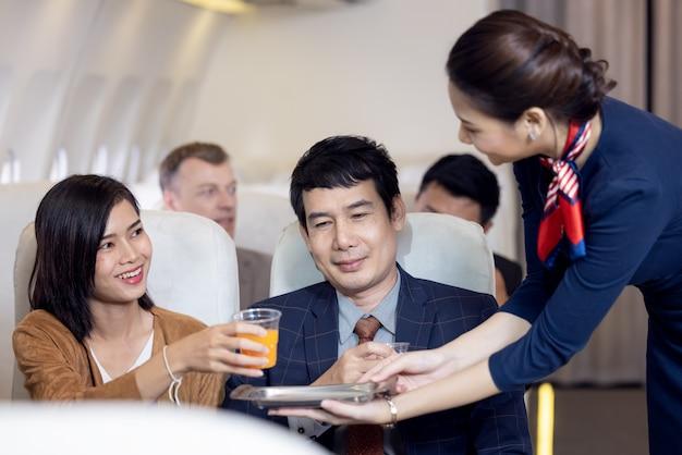 Il passeggero ha succo d'arancia servito da una hostess in aereo, gli assistenti di volo servono a bordo
