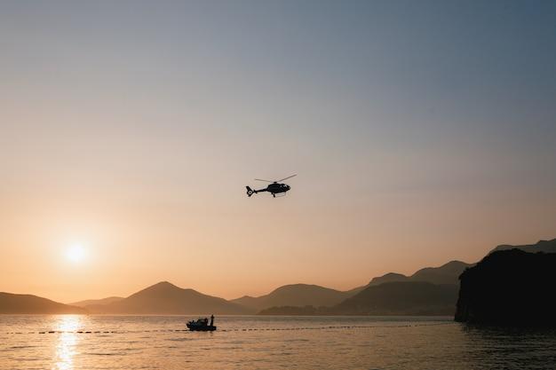L'elicottero del passeggero vola nel cielo sopra il mare e le montagne in montenegro