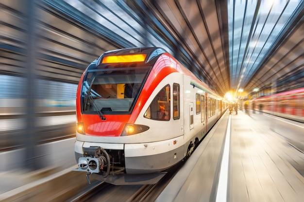 Treno passeggeri ad alta velocità con motion blur nella stazione.