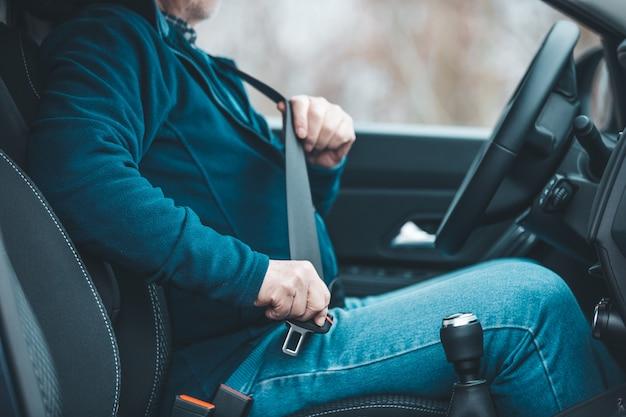 Uomo del passeggero che allaccia la cintura di sicurezza nel concetto di auto, trasporto e sicurezza
