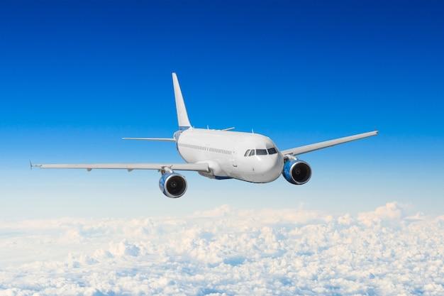 L'aereo passeggeri vola su un'altezza sopra le nuvole e il cielo blu.