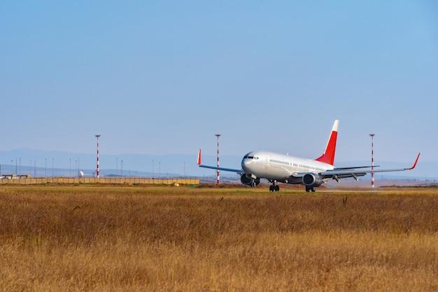Aereo passeggeri in decollo dalla pista dell'aeroporto in giornata di sole