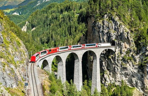 Treno passeggeri che attraversa il viadotto landwasser in svizzera