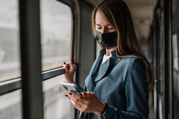 Passeggero in treno che indossa una mascherina medica