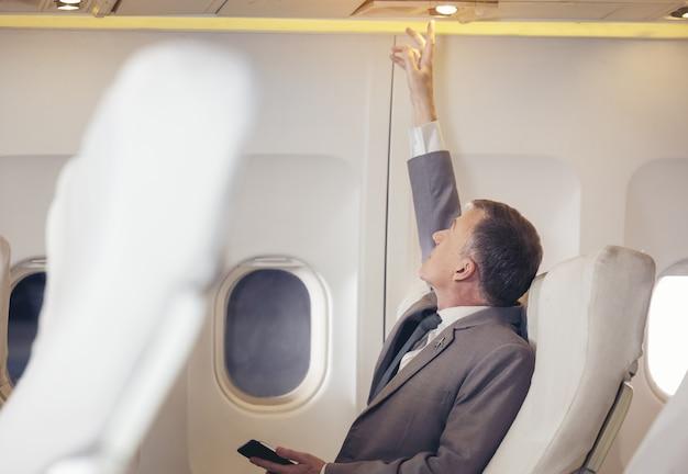 Viaggiatore del passeggero in aereo, viaggio in volo, uomo sulla luce in aereo