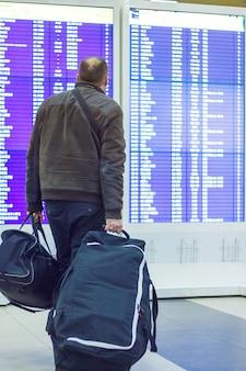 Passeggero con bagagli guardando il tabellone degli orari all'aeroporto