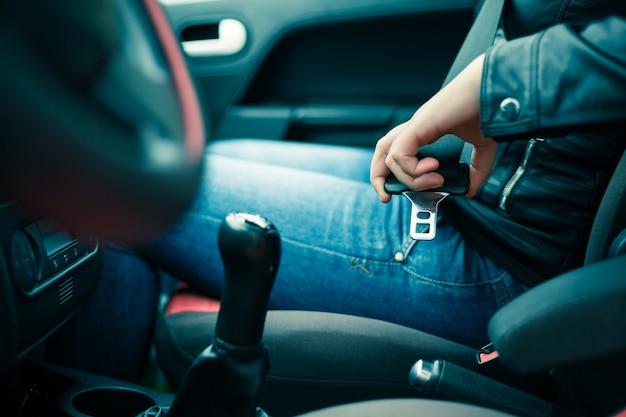Passeggero donna cintura di sicurezza di fissaggio in macchina, concetto di sicurezza