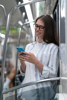 Passeggero giovane donna che utilizza smartphone mobile in chat nei social network in treno della metropolitana a metro