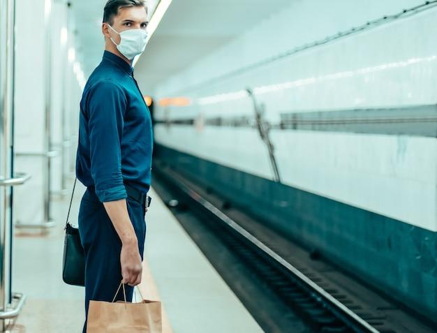 Passeggeri con maschere protettive in attesa del treno della metropolitana. coronavirus in città