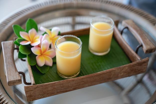 Bevanda cocktail di ghiaccio al frutto della passione su foglia di banana e vassoio in legno