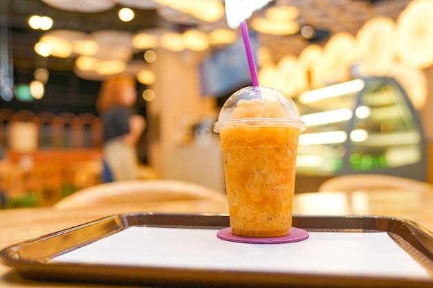 Frullato di frutto della passione in tazza di plastica da asporto nel ristorante.