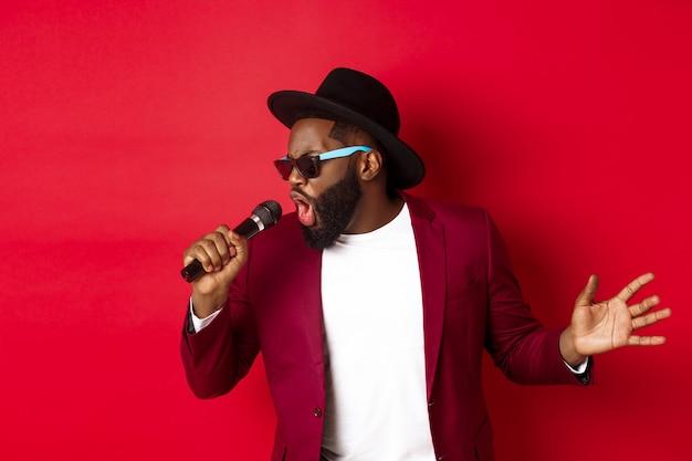 Cantante maschio nero appassionato che si esibisce su sfondo rosso, cantando nel microfono, indossando abiti da festa, in piedi su sfondo rosso.