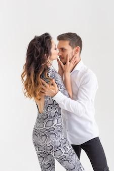 Appassionata coppia danzante sociale danse kizomba o bachata o semba o taraxia sul muro bianco con spazio di copia