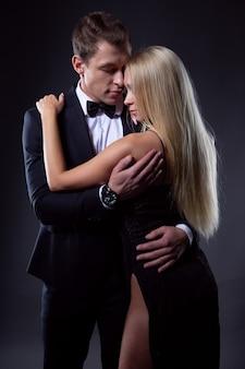 Una coppia appassionata, una donna con un'acconciatura leggera in un abito da sera nero e un bell'uomo in un vestito con un farfallino
