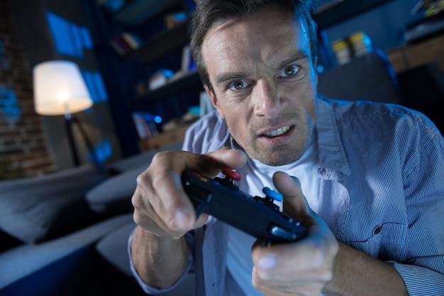 Appassionato e devoto uomo divertente che trascorre la serata cercando di superare un livello difficile mentre esplora un nuovo videogioco