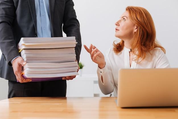 Appassionata e persistente bella signora che inizia una giornata in ufficio e riceve una pila di documenti