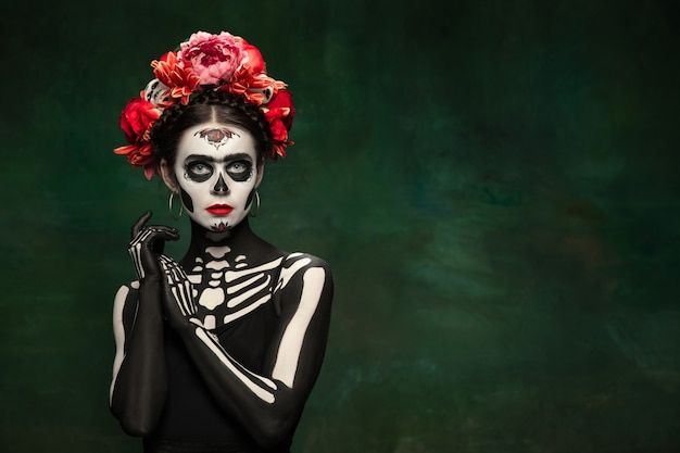 Appassionato. ragazza giovane come la morte di santa muerte saint o il teschio di zucchero con trucco luminoso. ritratto isolato su sfondo studio verde scuro con copyspace. festeggiando halloween o il giorno dei morti.