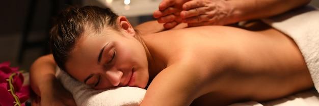 Liscivia passiva ragazza sul lettino da massaggio coperto con un asciugamano bianco e divertiti. l'uomo massaggia la schiena con la mano. candela bruciata in background.