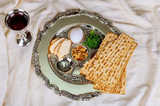 Fondo di pesach con la bottiglia di vino, il matzoh, il piatto dell'uovo e del seder