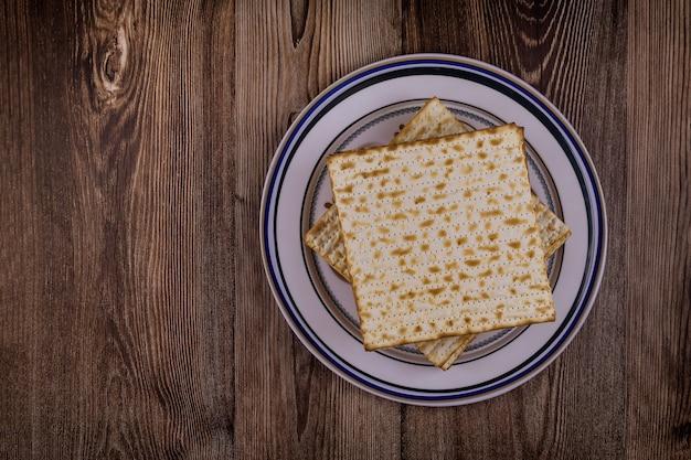 Celebrazione della pasqua ebraica con pane azzimo matzah kosher sul tradizionale piatto di pesach della pesach ebraica