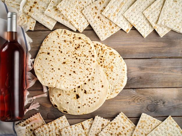 Pasqua concetto di vacanza con vino e pane azzimo su sfondo rustico, piatto laici.